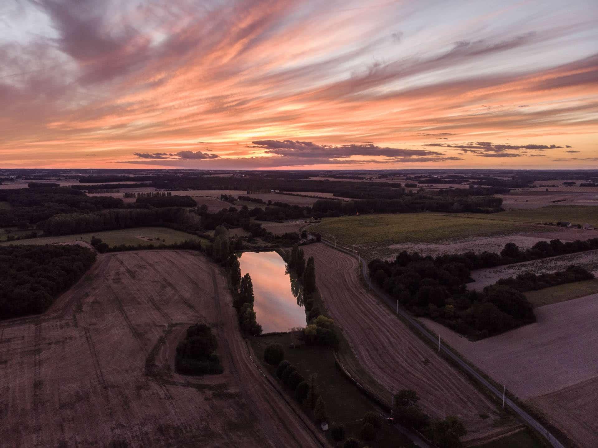 Prise de vue aérienne d'un coucher de soleil sur un étang au nord de Tours